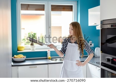 Happy housewife or chef in white kitchen apron with frying pan
