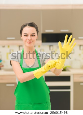 happy housewife putting on rubber gloves with home kitchen background - stock photo
