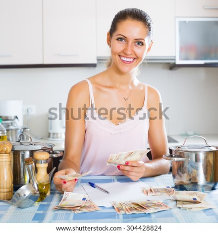 Happy housewife sitting at the table with money - stock photo