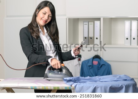 Happy housewife standing listening to music on her MP3 player while ironing the shirts at an ironing board with a smile of pleasure and enjoyment on her face - stock photo
