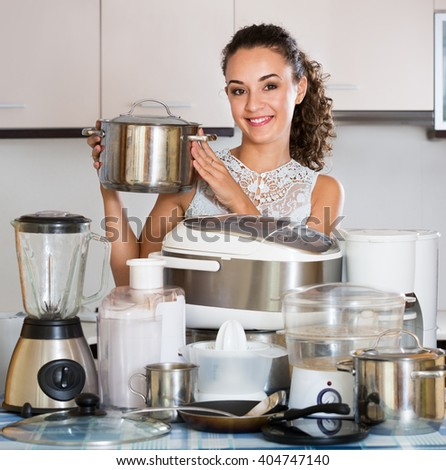 Happy housewife with a kitchen appliances at a home  - stock photo