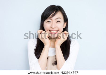Happy housewife with apron sing against light blue background