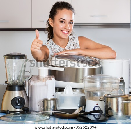 Happy housewife with kitchen appliances in the home