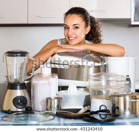Happy housewife with multicooker and other culinary appliances at home  - stock photo