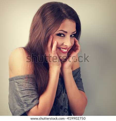 Happy humorous brunette woman holding the hands at face and giggling. Toned vintage portrait - stock photo