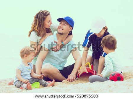 Happy husband and wife with three children in vacation at seaside