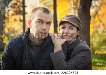 Happy husband hugging wife in autumn park, portrait, outdoor, fall - stock photo