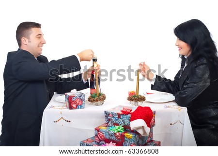Happy husband opening champagne bottle and preparing for toast with his wife at Christmas table