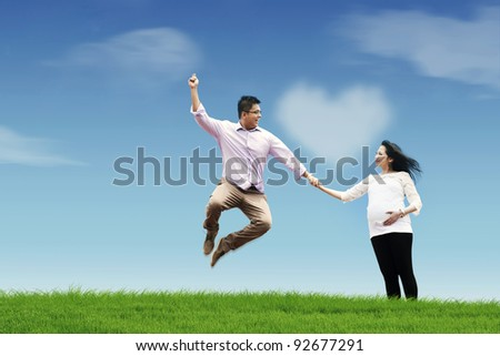 Happy husband with his pregnant wife holding hands in the field - stock photo