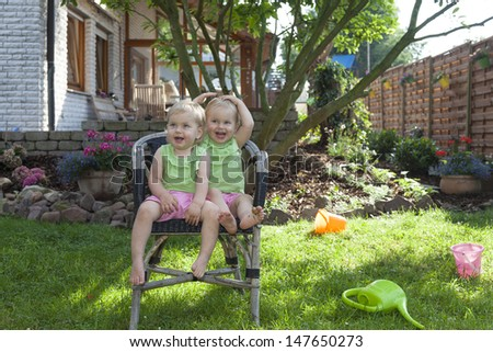 happy identical twin sisters at home in the garden, playing and having fun on a chair