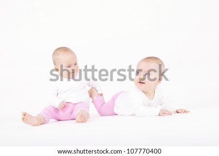 happy identical twin sisters playing on the ground
