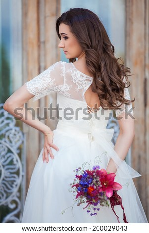 Happy, in love, beautiful bride with wedding bouquet flowers