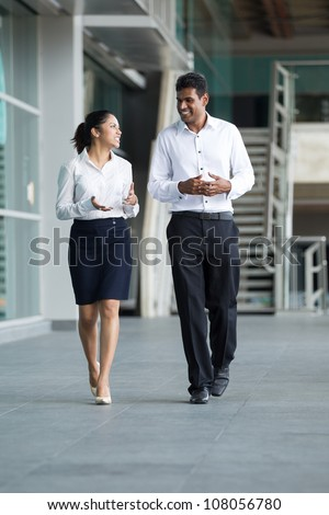 Happy Indian Business colleagues walking outside office & talking to each other. - stock photo