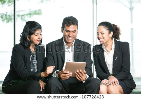 Happy Indian Business man and woman looking at a digital tablet.