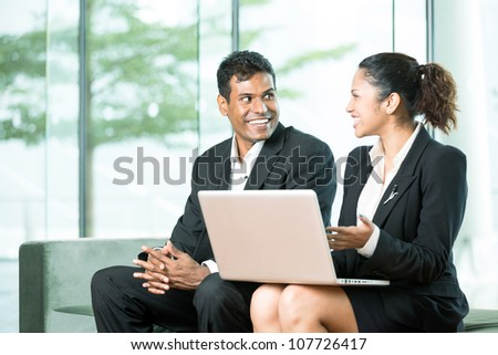 Happy Indian Business team working together around a laptop