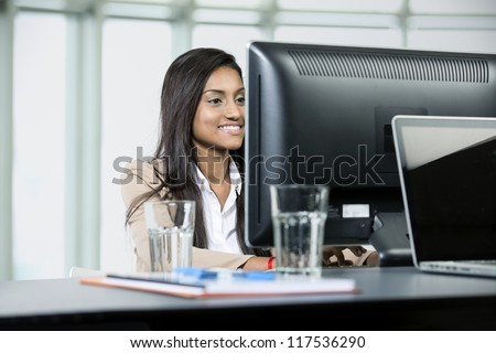 Happy Indian business woman at office desk working on a computer - stock photo