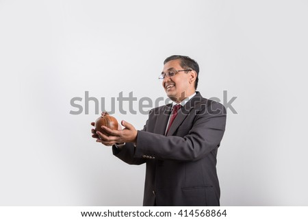happy indian businessman man holding piggy bank or money box made up of clay, clay money box & asian business man, isolated over white background, indian man with piggy bank, money box - stock photo