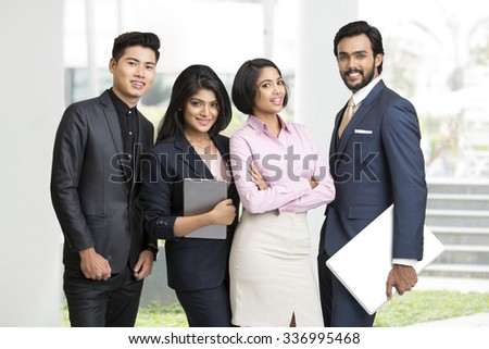 Happy Indian businessman standing with his team at office. - stock photo