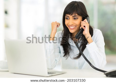 happy indian businesswoman receiving exciting news over the phone - stock photo