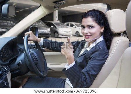 Happy indian businesswoman showing thumb up in the new car at the showroom - stock photo