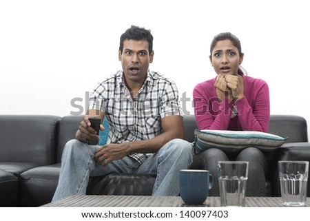 Happy Indian couple on the sofa watching tv in the living room