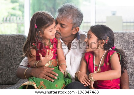 Happy Indian family at home. Asian father kissing her daughter, sitting on sofa. Parent and children indoor lifestyle. - stock photo