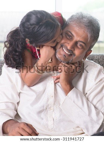 Happy Indian family at home. Asian girl kissing her father, sitting on sofa. Parent and child indoor lifestyle.