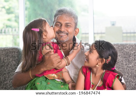 Happy Indian family at home. Asian girl kissing her father, sitting on sofa. Parent and children indoor lifestyle. - stock photo