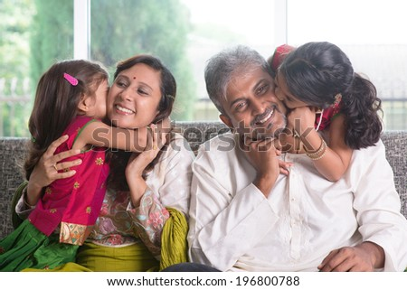 Happy Indian family at home. Asian girls kissing their parents, sitting on sofa. Parents and children indoor lifestyle.
