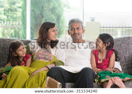 Happy Indian family at home. Asian parents bonding with their kids, sitting on sofa. Parents and children indoor lifestyle.