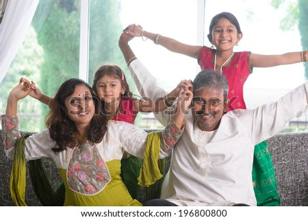 Happy Indian family at home. Asian parents playing with their kids, sitting on sofa. Parents and children indoor lifestyle. - stock photo