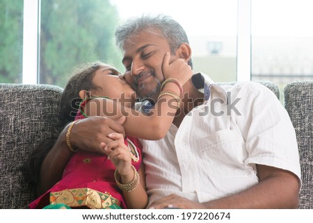 Happy Indian family at home. Asian sweet daughter kissing her father face indoor, sitting on sofa. - stock photo