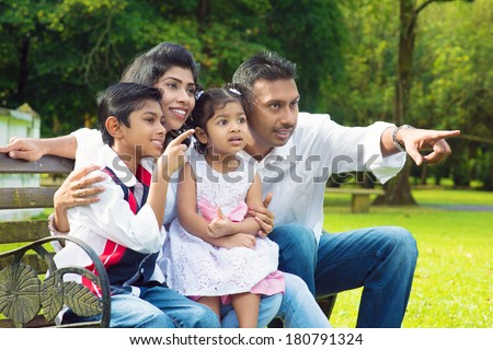 Happy Indian family at outdoor park. Candid portrait of parents and children having fun at garden park. Fingers pointing away. - stock photo