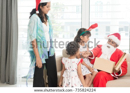 Happy Indian family celebrating Christmas day, with gift box and santa sitting on sofa or couch at home, Asian people festival mood indoors.