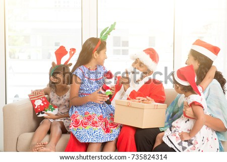 Happy Indian family celebrating Christmas holidays, with gift box and santa claus sitting on sofa or couch at home, Asian people festival mood indoors.