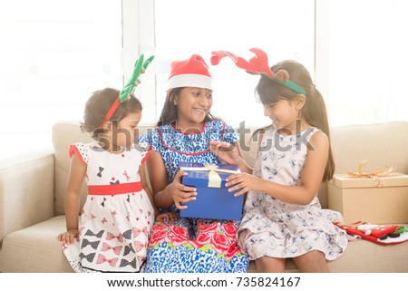 Happy Indian family celebrating Christmas holidays, with gift box and santa hat sitting on couch at home, cute Asian children on festival mood.