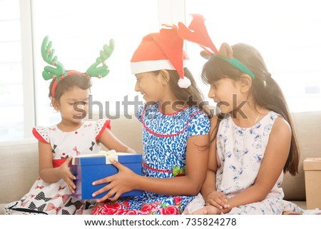 Happy Indian family celebrating Christmas holidays, with gift box and santa hat sitting on sofa at home, joyful Asian children on festival mood.