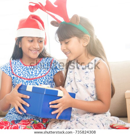 Happy Indian family celebrating Christmas holidays, with gift box and santa hat sitting on sofa at home, cute Asian children on festival mood.
