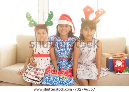Happy Indian family celebrating Christmas holidays, with gift box and santa hat sitting on sofa or couch at home, adorable Asian children on festival mood.