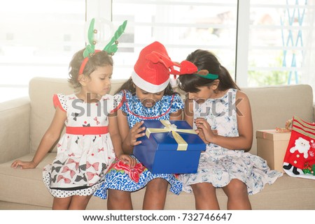 Happy Indian family celebrating Christmas holidays, with gift box and santa hat sitting on sofa or couch at home, cute Asian children on festival mood.