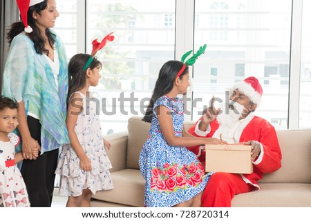 Happy Indian family celebrating Christmas holidays, with gift box and santa sitting on sofa at home, Asian people festival mood indoors.