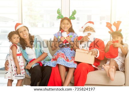 Happy Indian family celebrating Christmas holidays, with gift box and santa sitting on sofa at home, Asian parents and children festival mood indoors.