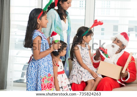 Happy Indian family celebrating Christmas holidays, with gift box and santa sitting on sofa or couch at home, Asian parents and children festival mood indoors.
