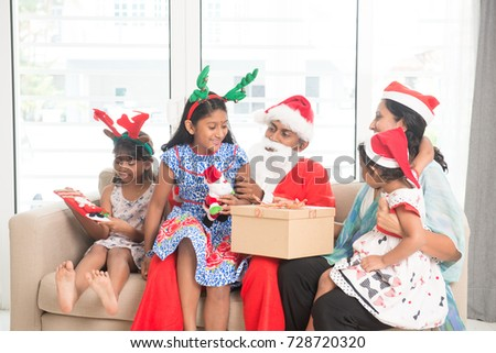 Happy Indian family celebrating Christmas holidays, with gift box sitting on sofa or couch at home, Asian people festival mood indoors.