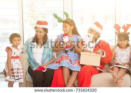 Happy Indian family celebrating Christmas holidays, with gift box sitting on sofa or couch at home, Asian parents and children festival mood indoors.