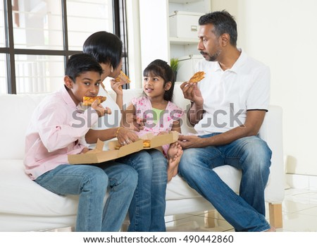 happy indian family eating pizza at home