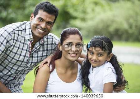 Happy Indian family. Father, mother and daughter in the park - stock photo