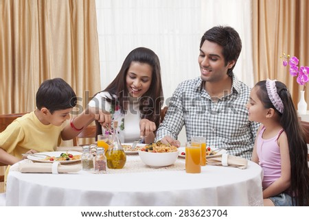 Happy Indian family having pizza together at restaurant - stock photo