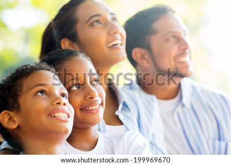 happy indian family outdoors looking up - stock photo