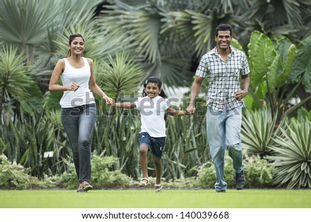Happy indian family running together outdoors in the park - stock photo